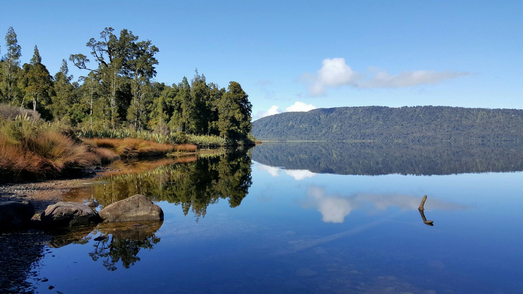 Het stille water van een meer in Nieuw Zeeland, langs de weg ergens